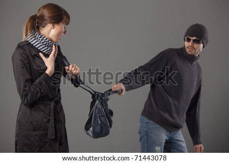 man mugging woman stealing her handbag - stock photo