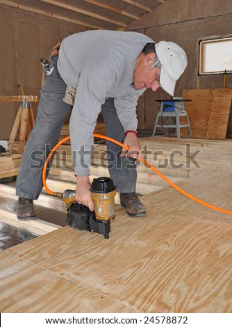 Man nailing plywood sub-floor with nail gun - stock photo