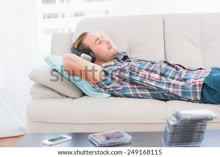 Man napping on sofa with music at home in the living room - stock photo