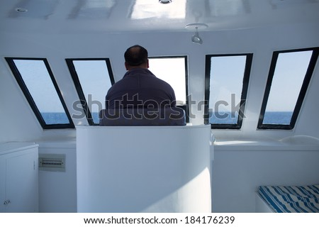 Man navigating a boat sitting in the captains chair during a cruise overlooking the ocean ahead, view from behind - stock photo