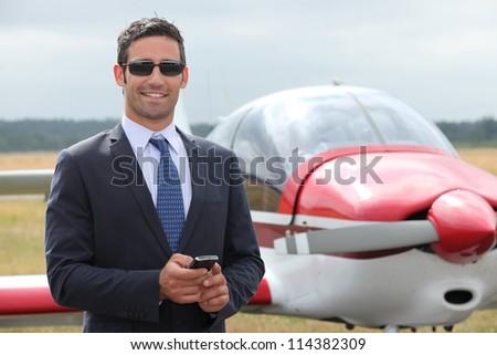 Man next to a light aircraft - stock photo