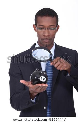 Man observing a piggy bank - stock photo