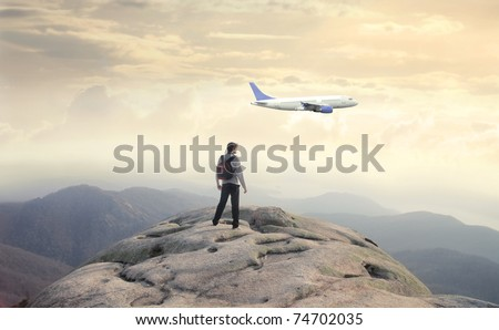 Man observing an airplane from a rock - stock photo
