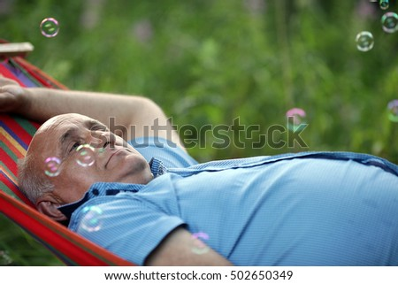 man of fifty years lying on a hammock on background of green grass