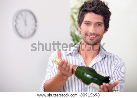 Man offering a bottle of champagne at five minutes to midnight - stock photo