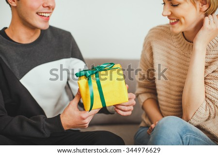 Man offering a present to girlfriend - stock photo