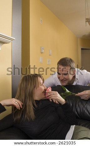 man offering flowers to a woman on couch for valentines