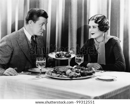 Man offering food to a woman in a restaurant - stock photo