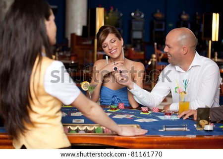 man offering young gorgeous woman two blackjack chips - stock photo