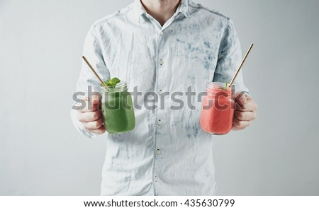 Man offers on camera two rustic jars with tasty cold green and red smoothies from kiwi and watermelon Healthy refreshment beverage for summer time with drinking straw inside - stock photo