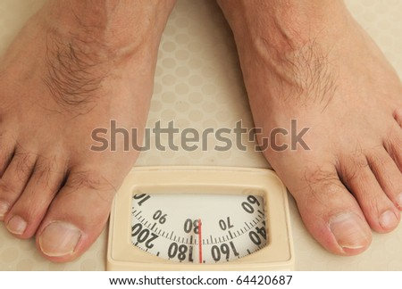 Man on a bathroom scale - stock photo