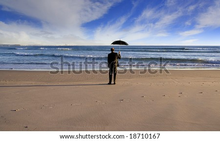 Man on a beach with umbrella - stock photo