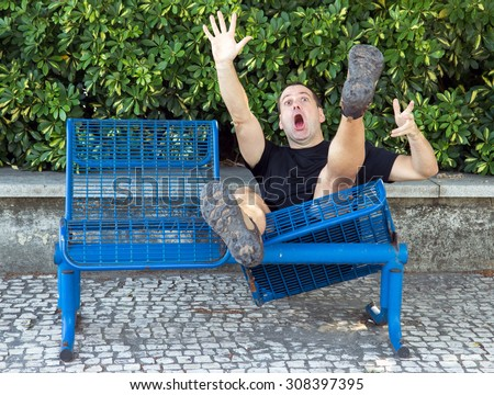 man on a bench falling down. Screaming man falls with a bench in the park. Damaged bench on street falls with sittings man. Shocked tourist falls down with bench. Accident on the trip while relaxing. - stock photo