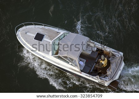 Man on a boat with outboard engine and fishing gear floats through blue sea waves in Denmark - stock photo