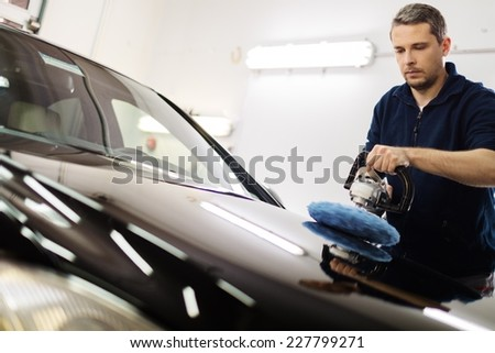 Man on a car wash polishing car with a polish machine  - stock photo