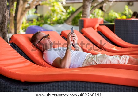 Man on a deck chair with smart phone on a summer day. Tourist calling by cell phone lying on the sunbed in a luxury hotel. Man relaxing in a tropical resort.