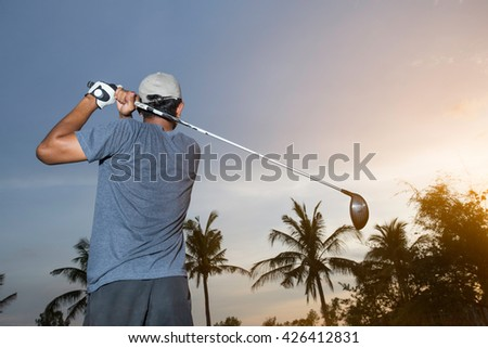Man on a golf course, playing golf in the sunshine.