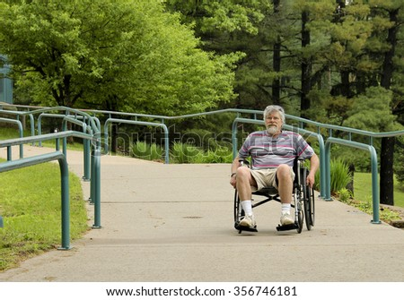 Man on a handicapped ramp in a wheelchair - stock photo
