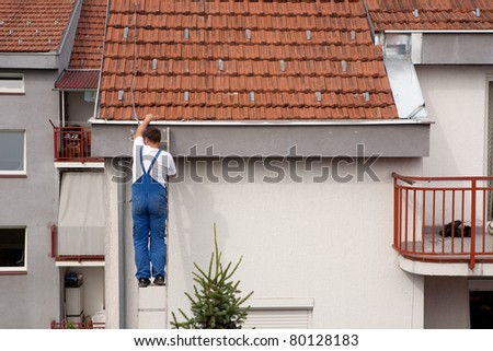 Man on a ladder climbing on the roof - stock photo