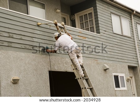 man on a ladder doing home repair