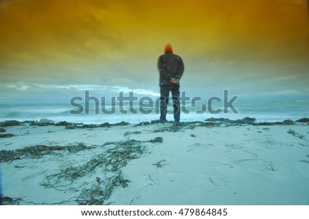 man on a log at a Beautiful orange sunset on the beach