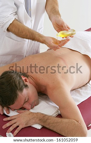 Man  on a massage table is having his low back massaged by a masseur putting oil - stock photo