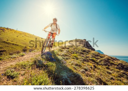 Man on a mountain bike races down the beautiful nature. Downhill - stock photo