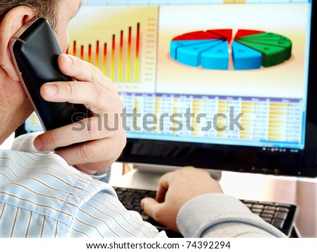 Man on a phone analyzing financial data and charts on computer screen. - stock photo