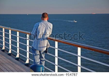 Man on a rail on a cruise ship - stock photo