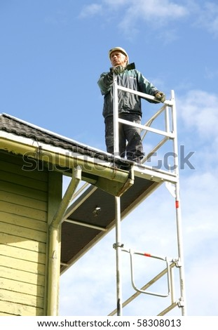 Man on a roof painting an old house - stock photo