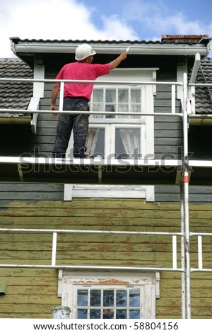 Man on a scaffold painting an old house - stock photo