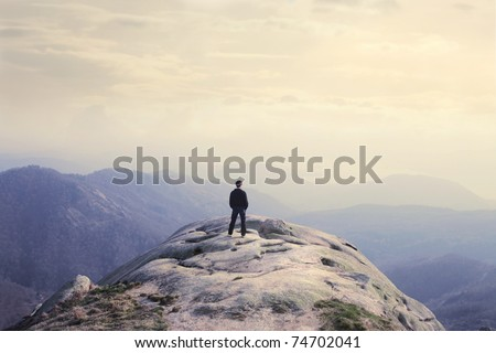 Man on a stone observing the landscape - stock photo