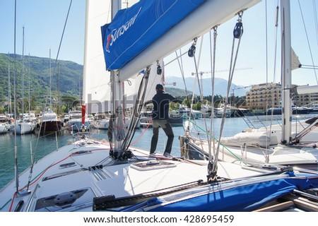 "Man on a yacht. Tivat, Montenegro - 26 April, 2016. Regatta ""Russian stream"" in God-Katorskaya bay of the Adriatic Sea off the coast of Montenegro. - stock photo"