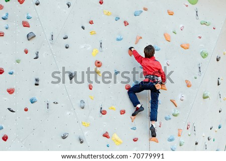 Man on artificial exercise climbing wall