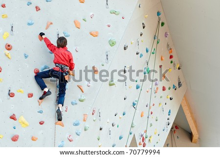 Man on artificial exercise climbing wall - stock photo