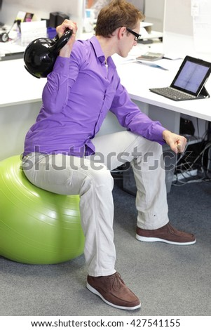 man on ball working out with kettle bell during office work