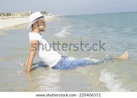 Man on beach lying in sand wearing hipster summer hat looking at the sea. Young male model enjoying summer travel holiday by the sea.