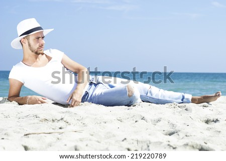 Man on beach lying in sand wearing hipster summer hat. Young male model enjoying summer travel holiday by the sea.