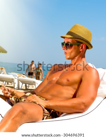 Man on beach sitting on beach chair looking to side smiling and typing sms on mobile phone,wearing hipster hat and military print trousers.Young male model enjoying summer travel holiday by the ocean. - stock photo