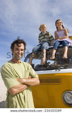Man on beach with arms crossed by son and daughter (5-9) on roof of camper van, portrait, low angle view - stock photo