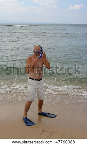 Man on beach with snorkel gear - stock photo