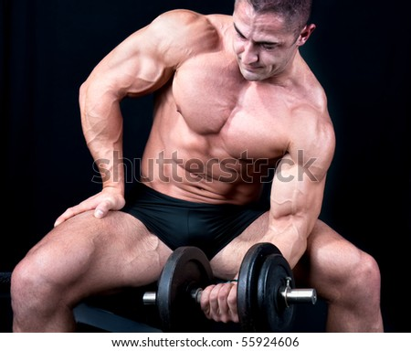 Man on bench with a bar weights in hands training, isolated on black - stock photo