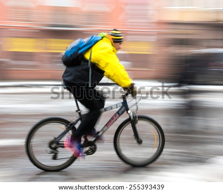 Man on bicycle in the city in a winter day. Intentional motion blur - stock photo