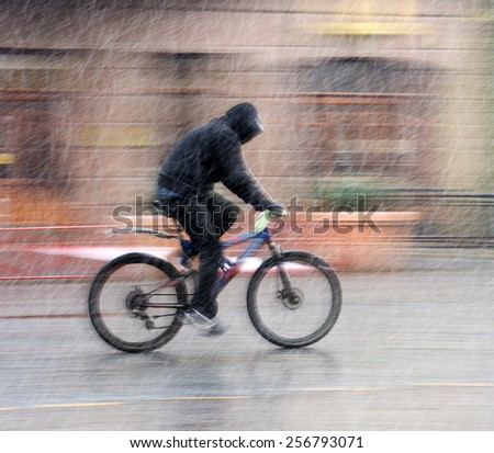 Man on bicycle in the city in snowy winter day.  Intentional motion blur - stock photo