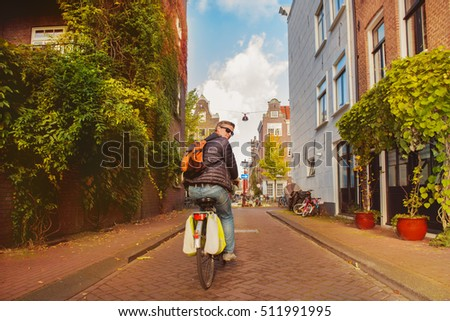 Man on bike in Amsterdam riding along narrow streets of the Dutch capital