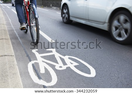 Man On Bike Using Cycle Lane As Traffic Speeds Past - stock photo
