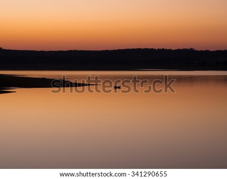 Man on boat at sunset in a lake - stock photo