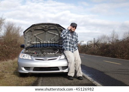 Man on cellphone with car trouble.
