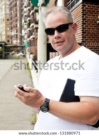 Man on city street with cell phone - stock photo