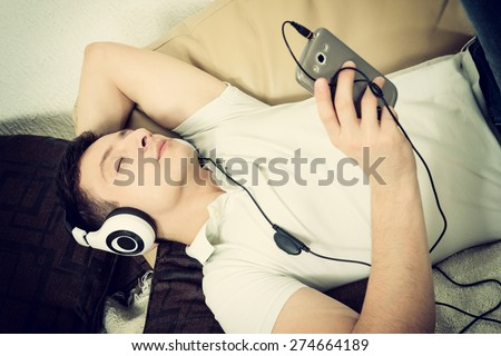Man on couch holding smartphone listening to music with headset daydreaming - stock photo